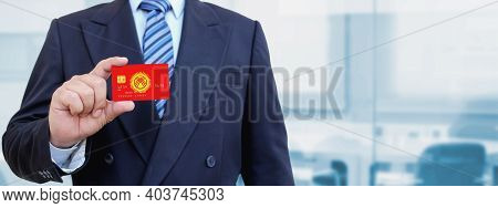 Cropped Image Of Businessman Holding Plastic Credit Card With Printed Flag Of Kyrgyzstan. Background