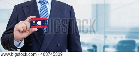 Cropped Image Of Businessman Holding Plastic Credit Card With Printed Flag Of Laos. Background Blurr