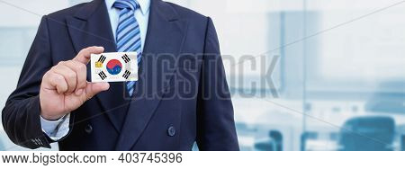 Cropped Image Of Businessman Holding Plastic Credit Card With Printed Flag Of South Korea. Backgroun