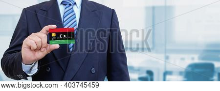Cropped Image Of Businessman Holding Plastic Credit Card With Printed Flag Of Libya. Background Blur