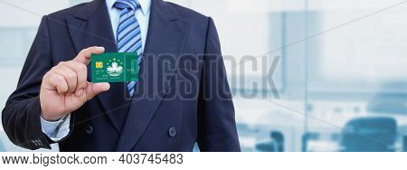 Cropped Image Of Businessman Holding Plastic Credit Card With Printed Flag Of Macau. Background Blur