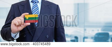 Cropped Image Of Businessman Holding Plastic Credit Card With Printed Flag Of Lithuania. Background