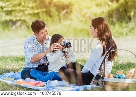 Happy Asian Young Family Father, Mother And Child Little Girl Having Fun And Enjoying Outdoor Picnic