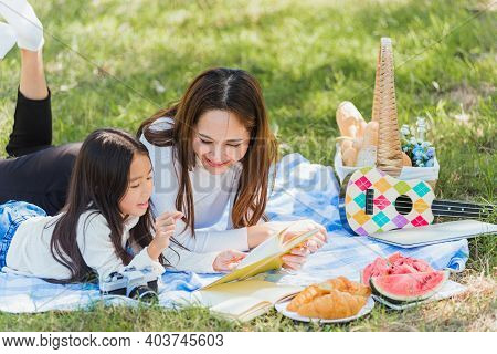 Happy Asian Young Family Mother And Child Little Girl Having Fun And Enjoying Outdoor Laying On Picn