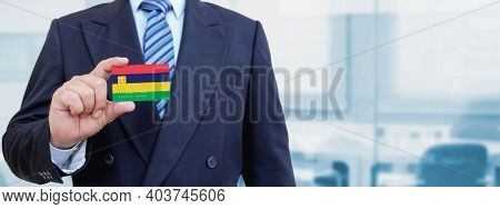 Cropped Image Of Businessman Holding Plastic Credit Card With Printed Flag Of Mauritius. Background