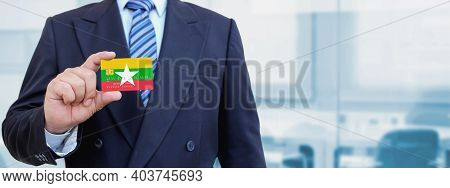 Cropped Image Of Businessman Holding Plastic Credit Card With Printed Flag Of Myanmar. Background Bl