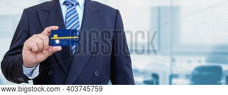 Cropped Image Of Businessman Holding Plastic Credit Card With Printed Flag Of Nauru. Background Blur