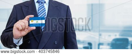 Cropped Image Of Businessman Holding Plastic Credit Card With Printed Flag Of Nicaragua. Background
