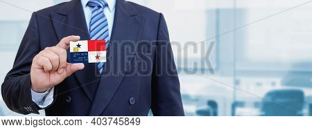 Cropped Image Of Businessman Holding Plastic Credit Card With Printed Flag Of Panama. Background Blu