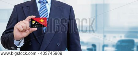 Cropped Image Of Businessman Holding Plastic Credit Card With Printed Flag Of Papua New Guinea. Back