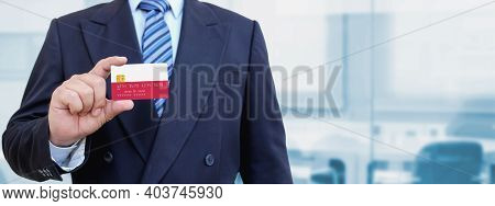 Cropped Image Of Businessman Holding Plastic Credit Card With Printed Flag Of Poland. Background Blu