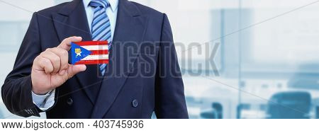 Cropped Image Of Businessman Holding Plastic Credit Card With Printed Flag Of Puerto Rico. Backgroun