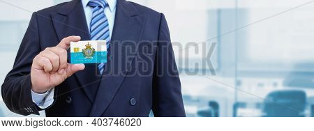 Cropped Image Of Businessman Holding Plastic Credit Card With San Marino. Background Blurred.
