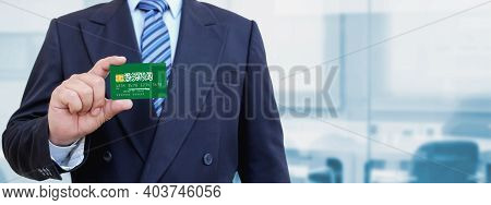 Cropped Image Of Businessman Holding Plastic Credit Card With Printed Flag Of Saudi Arabia. Backgrou