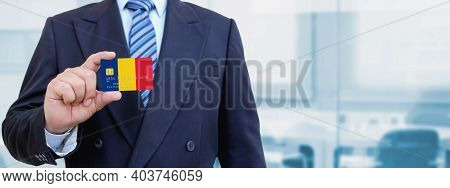 Cropped Image Of Businessman Holding Plastic Credit Card With Printed Flag Of Romania. Background Bl