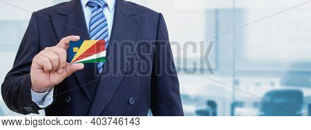 Cropped Image Of Businessman Holding Plastic Credit Card With Printed Flag Of Seychelles. Background