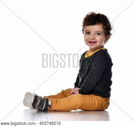 Side View Of A Handsome Stylish Baby Boy Sitting On White Background And Smiling. Child In A Sweater