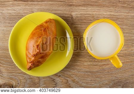 Baked Small Pie In Saucer, Yellow Cup Of Milk On Wooden Table. Top View