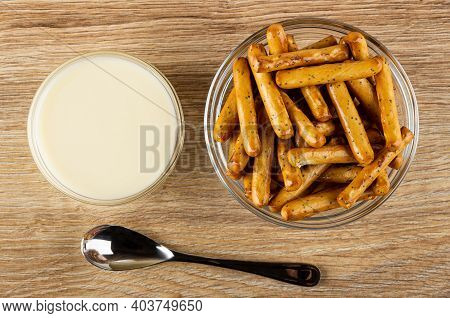 Condensed Milk In Glass Bowl, Breadsticks With Poppy In Transparent Bowl, Teaspoon On Brown Wooden T