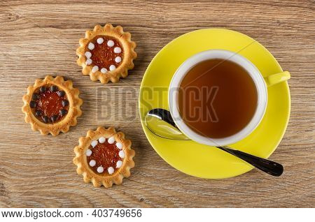 Three Cookies With Filling From Orange Jam And Chocolate, Teaspoon, Cup Of Tea On Yellow Saucer On W