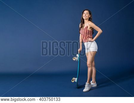Happy Young Asian Woman Standing And Holding Surfskate Or Skateboard On Blue Color Background, Exerc