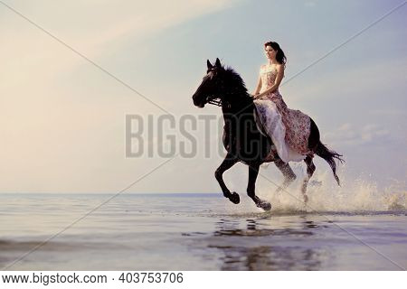 Woman on horse in dress rides along the seashore. Girl on beach with a big animal.