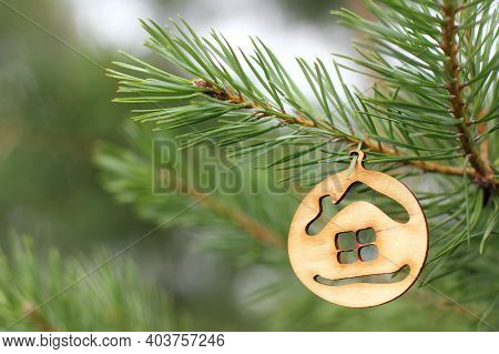 Wooden Decoration In The Shape Of A House Hanging On A Green Christmas Tree. Holiday Gift