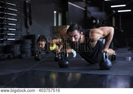 Sporty Man And Woman Doing Push-up In A Gym.