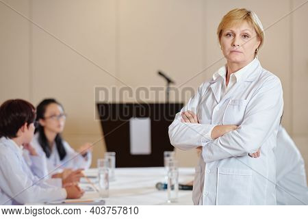Portrait Of Serious Female Researcher In Labcoat Folding Arms And Looking At Camera