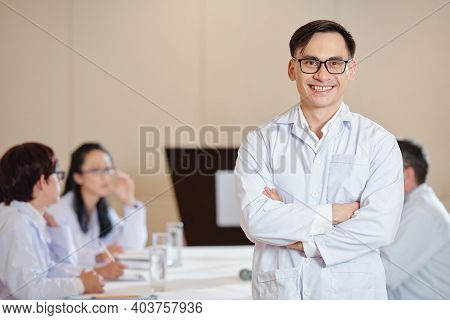 Portrait Of Happy Smiling Young Scientist In Labcoat Standing At Meeting Table With Arms Folderd And