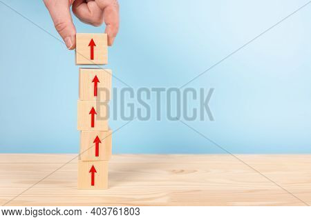 Hand Of Businessman Arranging Wooden Blocks Stacking With Red Arrow Up On Table, Blue Background, Bu