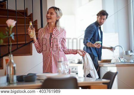 A young girl enjoying when her boyfriend doing housework at the kitchen. Kitchen, housework, home, relationship