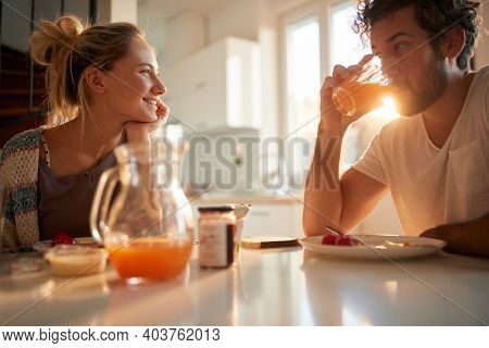 A young couple in love relaxing at the table after breakfast on a beautiful sunny morning at home. Relationship, love, together, breakfast