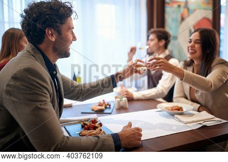 Young business people enjoying business lunch in a relaxed atmosphere at the restaurant. Business, restaurant, lunch