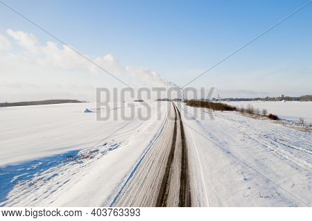 Snow-covered Road On The Background Of A Factory With Smoking Pipes Top View.