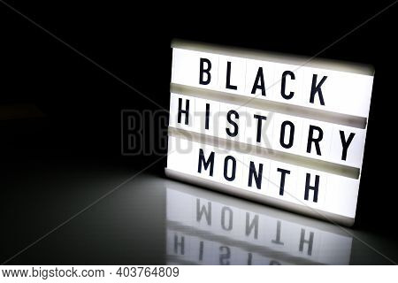 Lightbox With Text Black History Month On Dark Black Background With Mirror Reflection. Message Hist