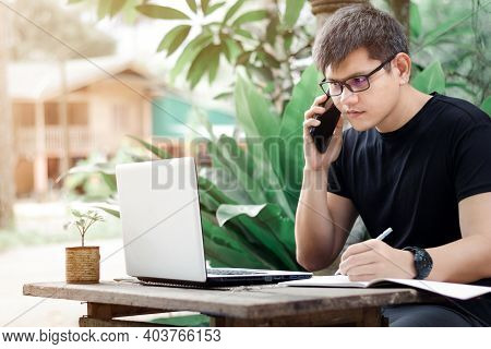 Young Business Man Talking On The Phone On The Weekend, Male Freelancer Working With Laptop Freelanc