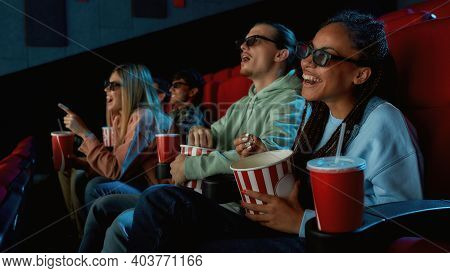 Happy Young Woman Wearing Glasses, Eating Popcorn While Watching Movie In Cinema Auditorium Together