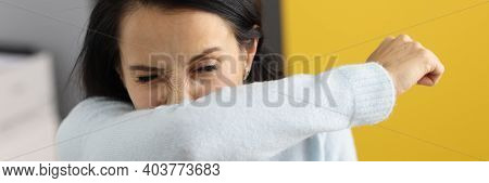 Young Woman Sneezes Into Her Elbow. Virus Spreading Through Sneezing Concept