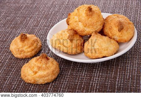 Coconut Cookies In White Glass Plate, Two Cookies On Dark Mat