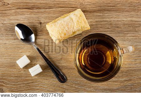 Sugar Cubes, Teaspoon, Puff Cookie, Transparent Cup With Tea On Brown Wooden Table. Top View