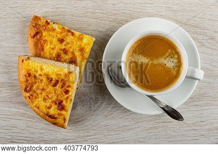 Two Pieces Of Baked Flatbread With Cheese, Spoon, Black Coffee In Cup On Saucer On Wooden Table. Top