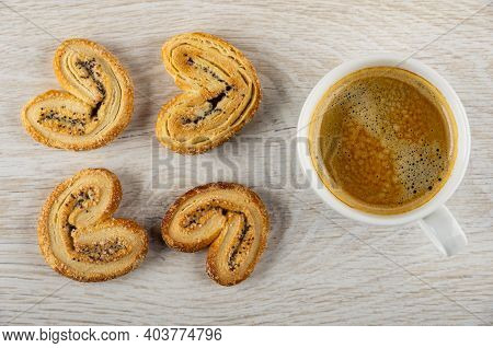 Few Puff Cookies With Poppy Seeds, Black Coffee In White Cup On Wooden Table. Top View