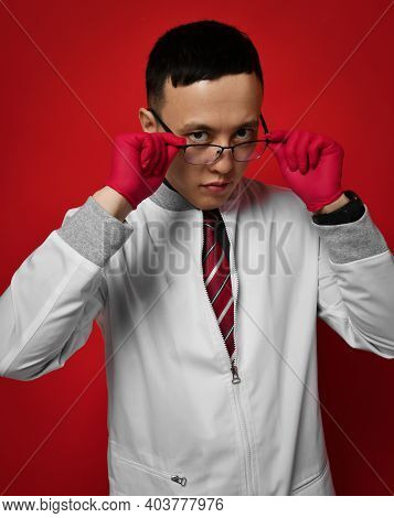 Portrait Of Young Man Doctor Urologist Or Proctologist In Medical Gown And Gloves Putting On Taking
