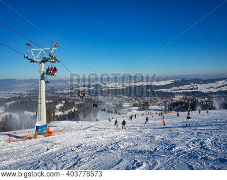 Ski Slope, Chairlift, Skiers And Snowboarders In Bialka Tatrzanska Ski Resort In Poland In Winter. S