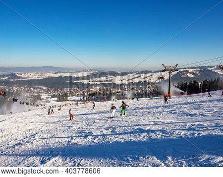 Ski Slopes, Chairlifts, Skiers And Snowboarders In Bialka Tatrzanska Ski Resort In Poland In Winter.