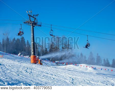 Ski Lift (chairlift) With Unrecognizable Skiers, Ski Slope And Snow Cannons In Action In Bialka Tatr