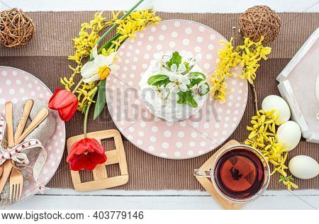 Bright Easter Composition With Homemade Easter Cake On A Plate, Flowers, Tea, Eggs. Easter Holiday C