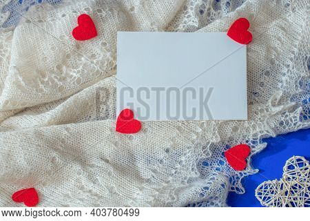 Valentine Scene With White Shawl, Rattan And Felt Red Hearts, Paper Card Note On Blue Background. Lo