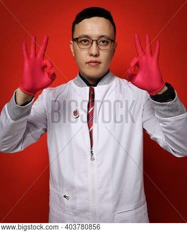 Portrait Of Young Man Doctor Urologist Or Proctologist In White Medical Gown And Red Latex Gloves Ge